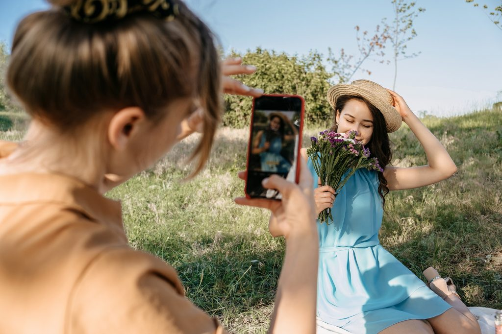 Back view of Young woman holding cell phone and making photo of her girl friend. Two girlfriends take pictures of each other on Smartphone camera on nature background. Summer holidays and technology