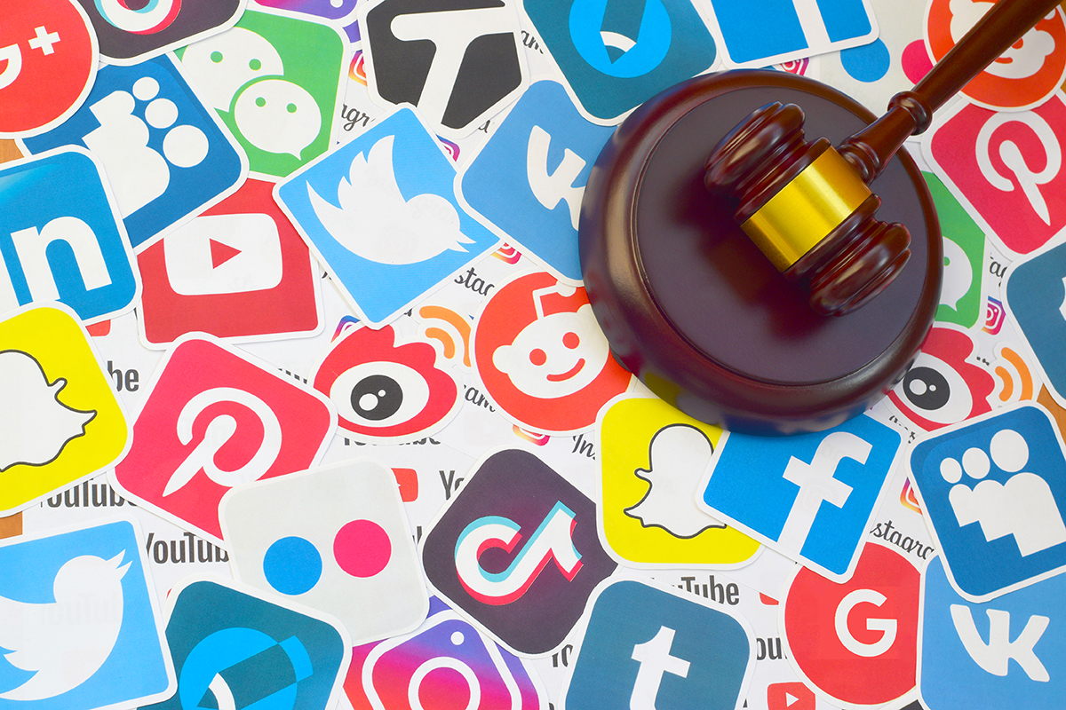 Wooden judge gavel lies on many paper logos of popular social networks and internet resources. Entertainment lawsuit concept