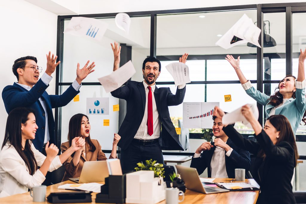 Successful group of casual business relaxing and throwing paper winning success agreement.Creative business people celebrating with arms up.Teamwork and success concept